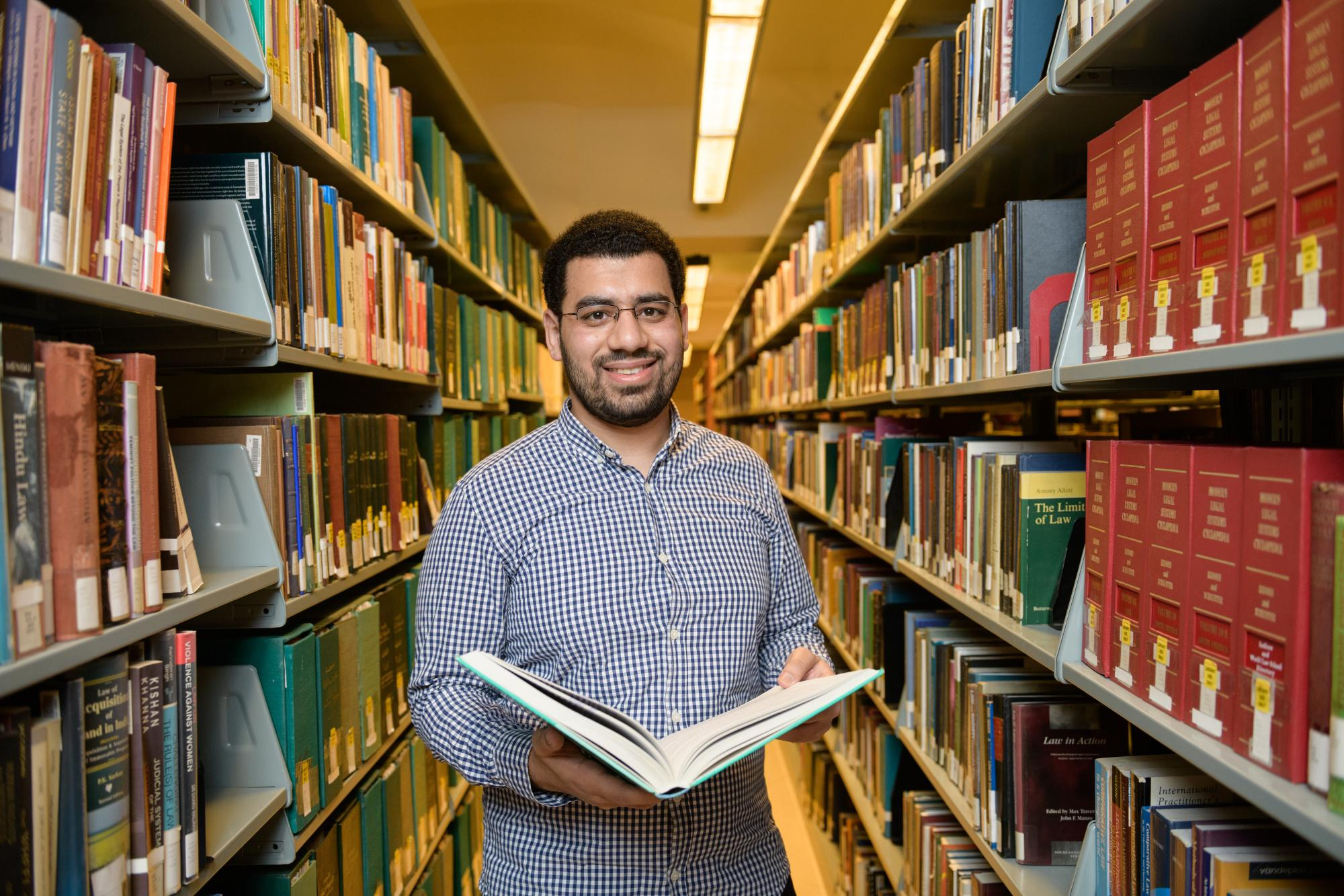 Student checking book shelves in a library